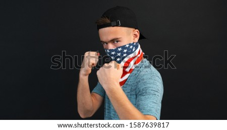 Focused teenager boy covered face with scarf USA boxing his hands virtually at camera, causing close-up enemy on black background. Protest, sport, training, youth. Teenage lifestyle. Healthy lifestyle