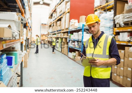 Focused warehouse worker with clipboard in a large warehouse #252243448