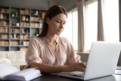 Focused woman journalist freelancer working online on laptop, sitting at desk at home, looking at screen, typing, serious young female writing blog or chatting with friends in social network