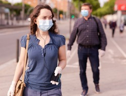 Focused woman wearing medical mask and rubber gloves listening to music on earphones on way to work along city street on spring day. New life reality during COVID 19 pandemic