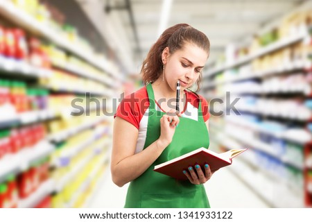 Focused woman working at hypermarket or supermarket making thinking gesture using pen to touch chin with notebook in hand Foto stock ©
