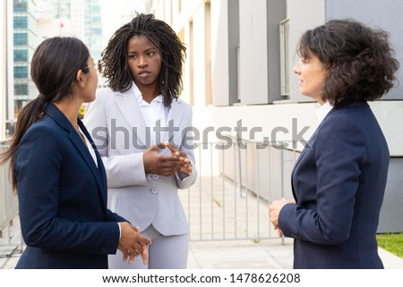 Focused women talking while standing near office building. Confident managers wearing suits communicating outdoor. Business confidence concept