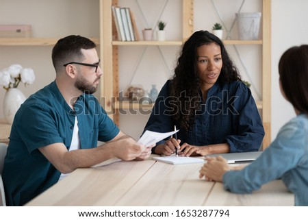Focused young african american female supervisor holding meeting with teammates, brainstorming ideas. Diverse business people discussing working issues, summarizing project results at office.