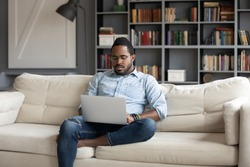 Focused young african american freelancer businessman sitting on sofa with laptop, working remotely online from home. Concentrated millennial multiracial guy studying distantly alone in living room.