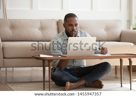 Focused young african american man studying or working on laptop sit on floor in living room, serious black male student freelancer using looking at computer writing notes doing research at home