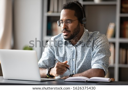 Photo of Focused young african businessman wear headphones study online watching webinar podcast on laptop listening learning education course conference calling make notes sit at work desk, elearning concept