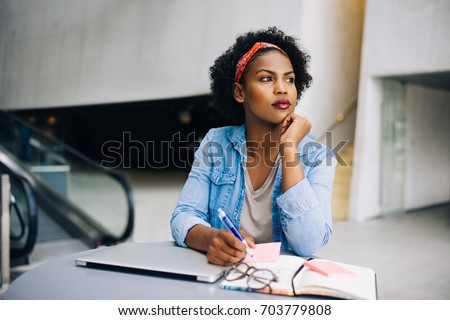 Focused young African female entrepreneur deep in thought while working at a table in a modern office building lobby