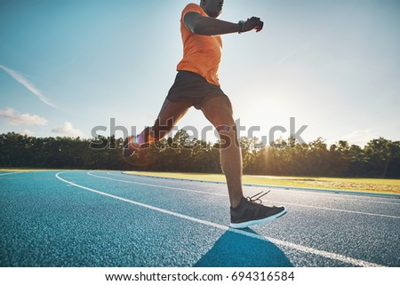 Focused young African male athlete in sportswear sprinting alone down a running track on a sunny day #694316584