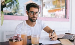Focused young bearded male freelancer in eyeglasses and casual clothes writing notes with pen on paper while working on laptop at table with glass of fresh beverage in modern outdoor cafe