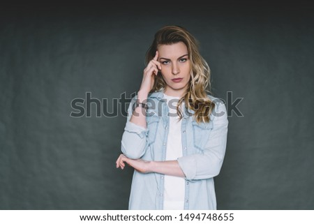 Focused young blond woman in casual outfit touching temple while concentrating and remembering in studio on gray background #1494748655