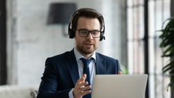 Focused young businessman manager wearing headset with microphone, involved in distant online meeting with colleagues or partners, discussing working issues using video call computer application.