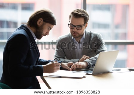 Focused young businessman signing agreement with skilled lawyer in eyeglasses. Concentrated financial advisor showing place for signature on paper contract document to male client at meeting in office Photo stock ©