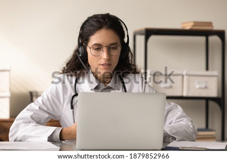 Focused young Caucasian female doctor in headphones look at computer screen talk on video call with patient. Woman GP in medical uniform and earphones have webcam online digital virtual with client.