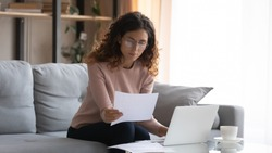 Focused young Caucasian woman in glasses sit on couch at desk work on laptop read paperwork, concentrated millennial businesswoman manage paper documents, pay bills or taxes, use computer at home