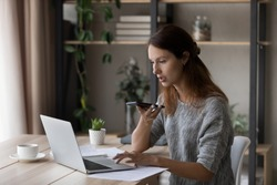 Focused young Caucasian woman sit at desk at home work on laptop record audio message on cellphone, millennial female use computer browsing, activate virtual digital voice assistant on smartphone