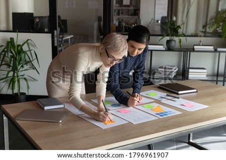 Focused young indian employee managing working processes with smart skilled 30s blonde female boss, using colorful stickers on paper documents at office table, teamwork brainstorming activity.
