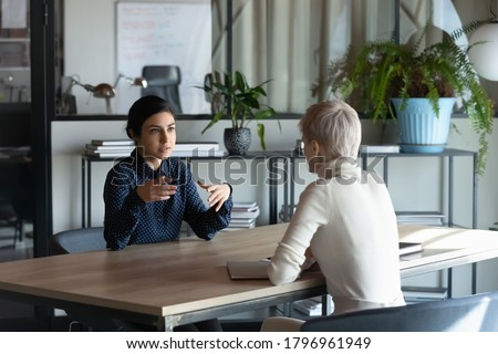 Focused young indian job seeker self-presenting on interview with confident european hr manager or company leader. Skilled multiracial manager giving professional consultation to client in office.