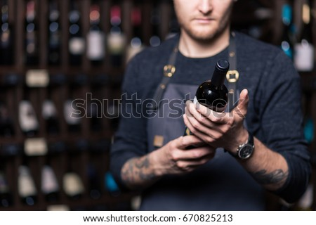 Focused young male sommelier in suite looking at red wine in bottle #670825213