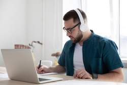 Focused young man businessman company worker employee in glasses wearing wireless headphones, watching educational webinar lecture seminar on laptop online, writing down notes in modern office.