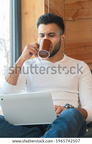 Focused young man sipping coffee and working on his laptop. Sitting next to the window in a peaceful cozy room. Wearing a white shirt and jeans. Winter season in the city of Zakopane, Poland.  Stock photo ©