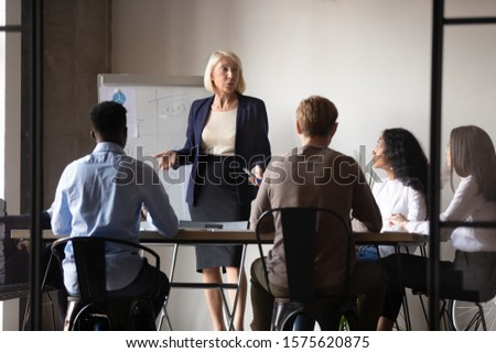 Focused young mixed race colleagues listening to middle aged female boss presenting marketing strategy near whiteboard. Confident older businesswoman speaker giving educational workshop at office.
