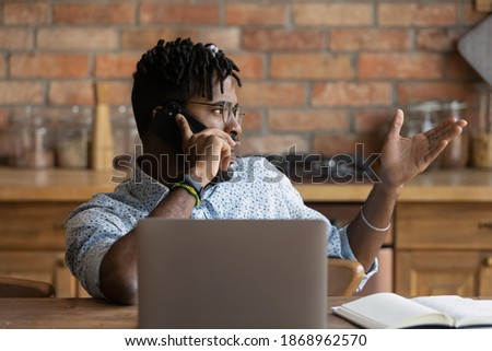 Focused young multiracial businessman discussing project with client by cellphone call conversation, helping solving problem, communicating distantly working alone at home office, multitasking concept Stock photo ©