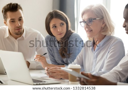 Focused young students interns workers making notes listening to old senior aged female manager coach mentor leader teacher talking at group office meeting instructing business work team with laptop