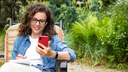 Focused young woman in headphones using smartphone sitting on chair in park garden outdoor,writing notes.Smiling curly female student watching online webinar,learning language,listening audio course