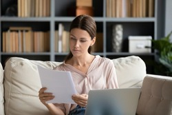 Focused young woman sit on couch in living room working on laptop considering paperwork correspondence, serious millennial female read paper contract or notice use computer at home