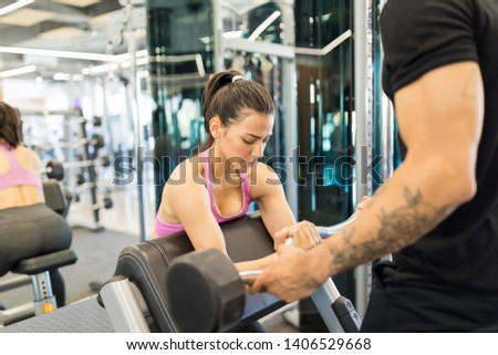 Focused young woman training with the help of personal trainer in health club
