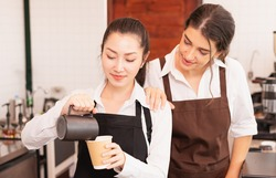 Focusing on half-body angle of Asian barista women fill milk into hot coffee cup, caucasian barista woman cheering to prepare coffee in cafe bar. Barista work at coffee bar and food service business