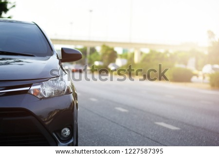 Focusing on the Dark Gray car headlights on a street corner with sunlight flares, In the background, the driver, bike and car. Closeup headlights of car. Car parking on the street #1227587395