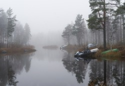 Fog. A few boats lie on the shore of the lake near some birch trees.