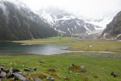 fog and rain on a cold spring day in the alps, the hohe tauern national park in austria, on a mountain lake