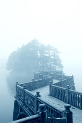 fog and zigzag bridge in the lake