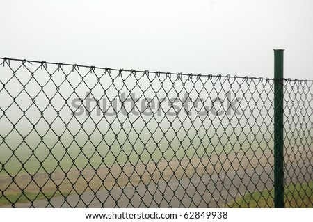 Fog behind the wire fence
