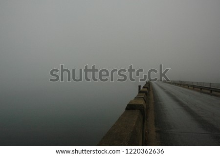 Fog-bound road along endless water #1220362636