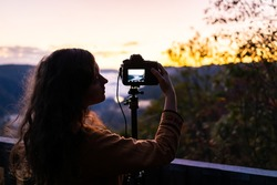 Fog clouds on mountains with woman photographing timelapse in morning at new river gorge valley in Grandview Overlook, West Virginia during sunrise