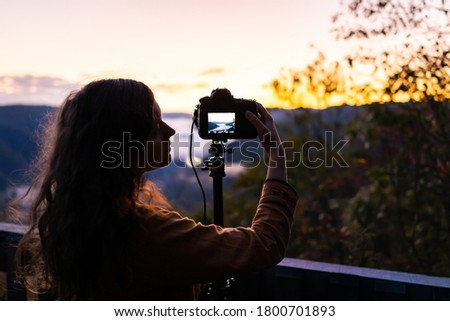 Photo of  Fog clouds on mountains with woman photographing timelapse in morning at new river gorge valley in Grandview Overlook, West Virginia during sunrise