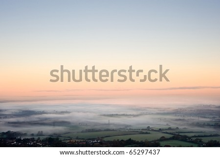 Fog covered English countryside at sunrise looking North from Devil's Dyke over the Weald on the South Downs with vibrant colorful sky