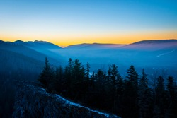 Fog in the valley and colorful sunset over the mountain ridge. Dark coniferous forest growing on a rock, Tatra Mountains, Poland. Selective focus on the hills, blurred background.