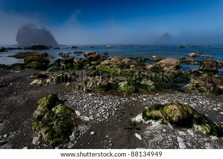 Fog lifts on a rocky beach with and offshore islands
