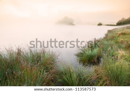 Fog mist landscape over lake in Autumn Fall with vibrant colors