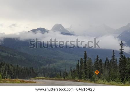 Fog on road through mountain pass (British Columbia. Canada) - stock photo