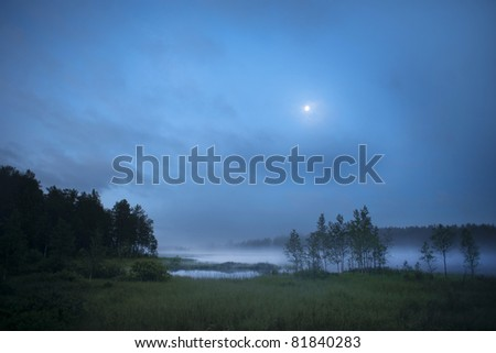 Fog over a lake in early morning in Halsingland, Sweden