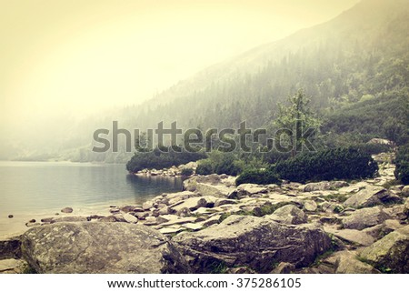 Fog over mountains lake. Nature conceptual image. Morskie Oko in Tatry, Poland. Vintage colors picture.