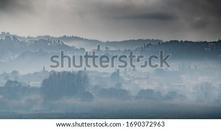 Fog over the city on a slope in cloudy weather, cypresses stick out, Corfu, Greece ストックフォト ©