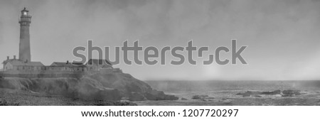 Fog rolls in on Pigeon Point Lighthouse with sun still shinning in black and white