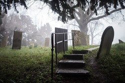 Foggy eerie graveyard with mist and creepy fog around headstones. Grave stones peaceful atmosphere old abandoned derelict English church yard misty spooky sinister trees for funeral burial service