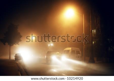 Foggy fog city street lights and car traffic at night